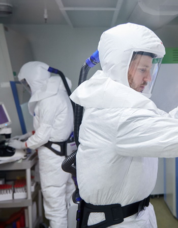 Two people in a lab wearing PPE and working